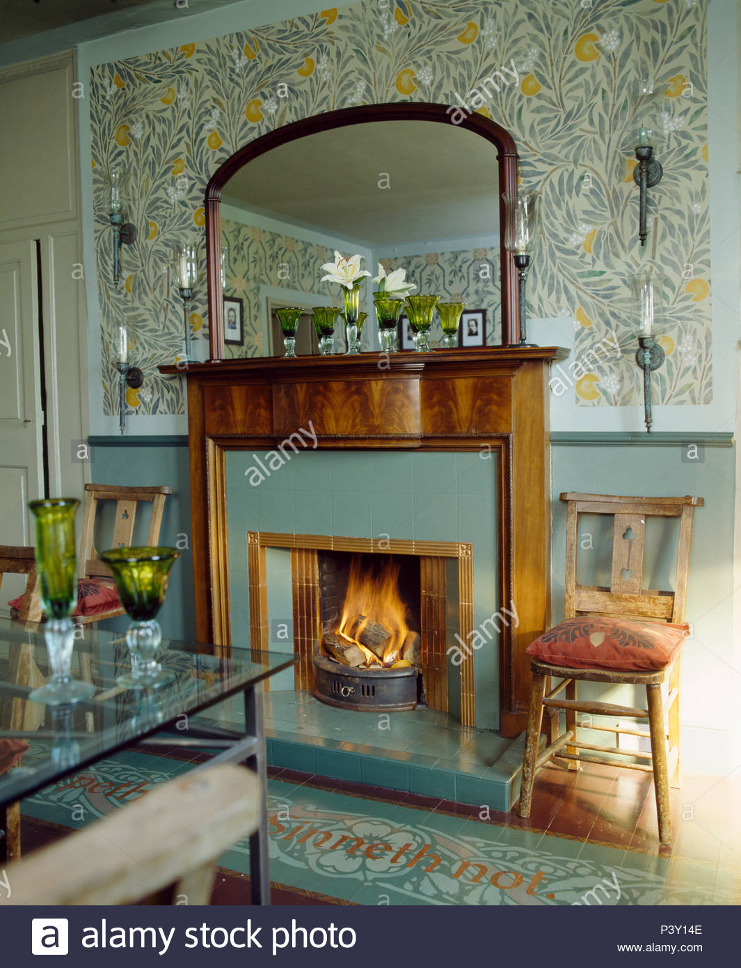 stencilled artscrafts pattern on wall above fireplace with lighted fire in country dining room P3Y14E