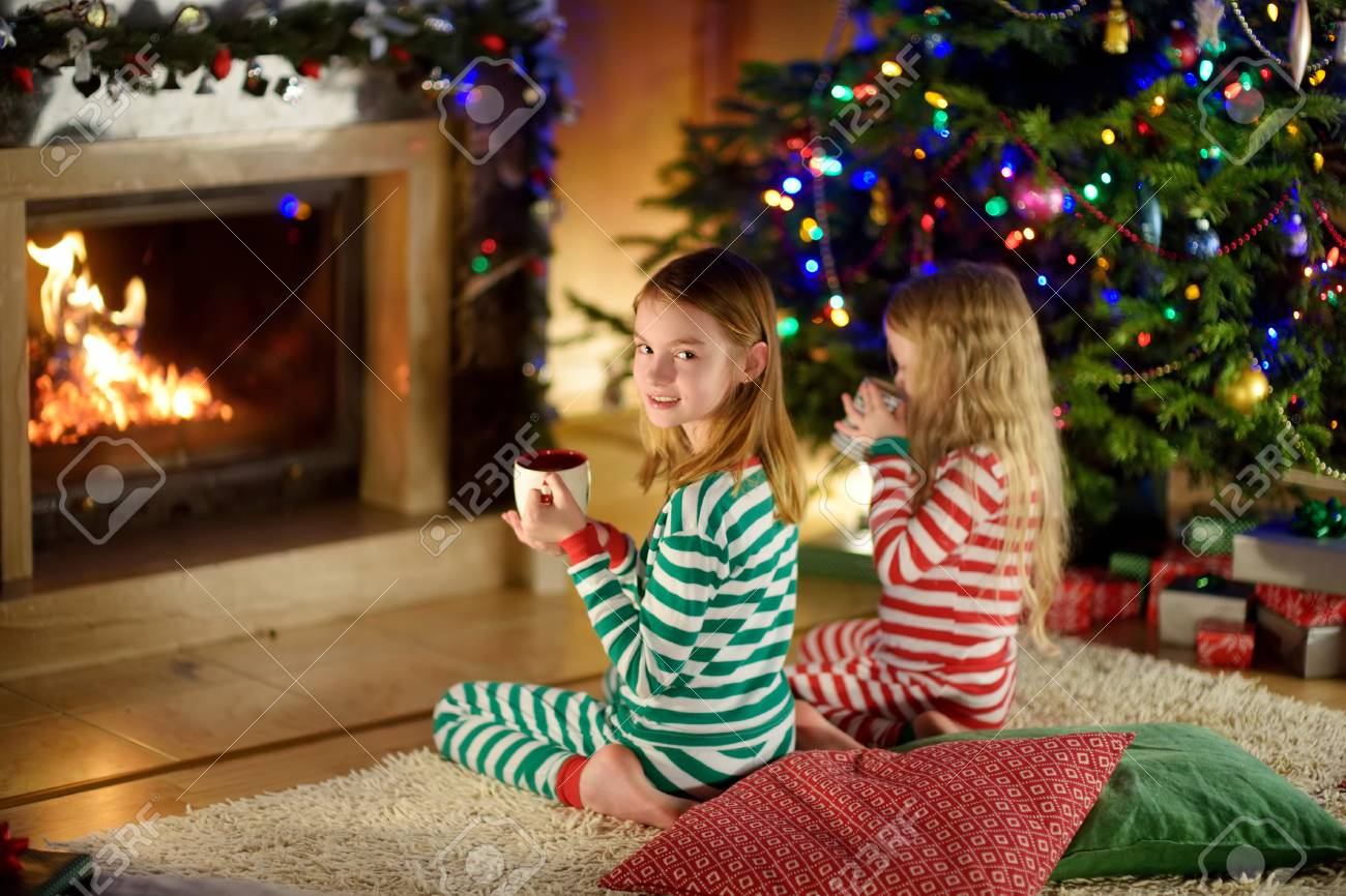 two cute happy girls having hot chocolate by a fireplace in a cozy dark living room on christmas eve