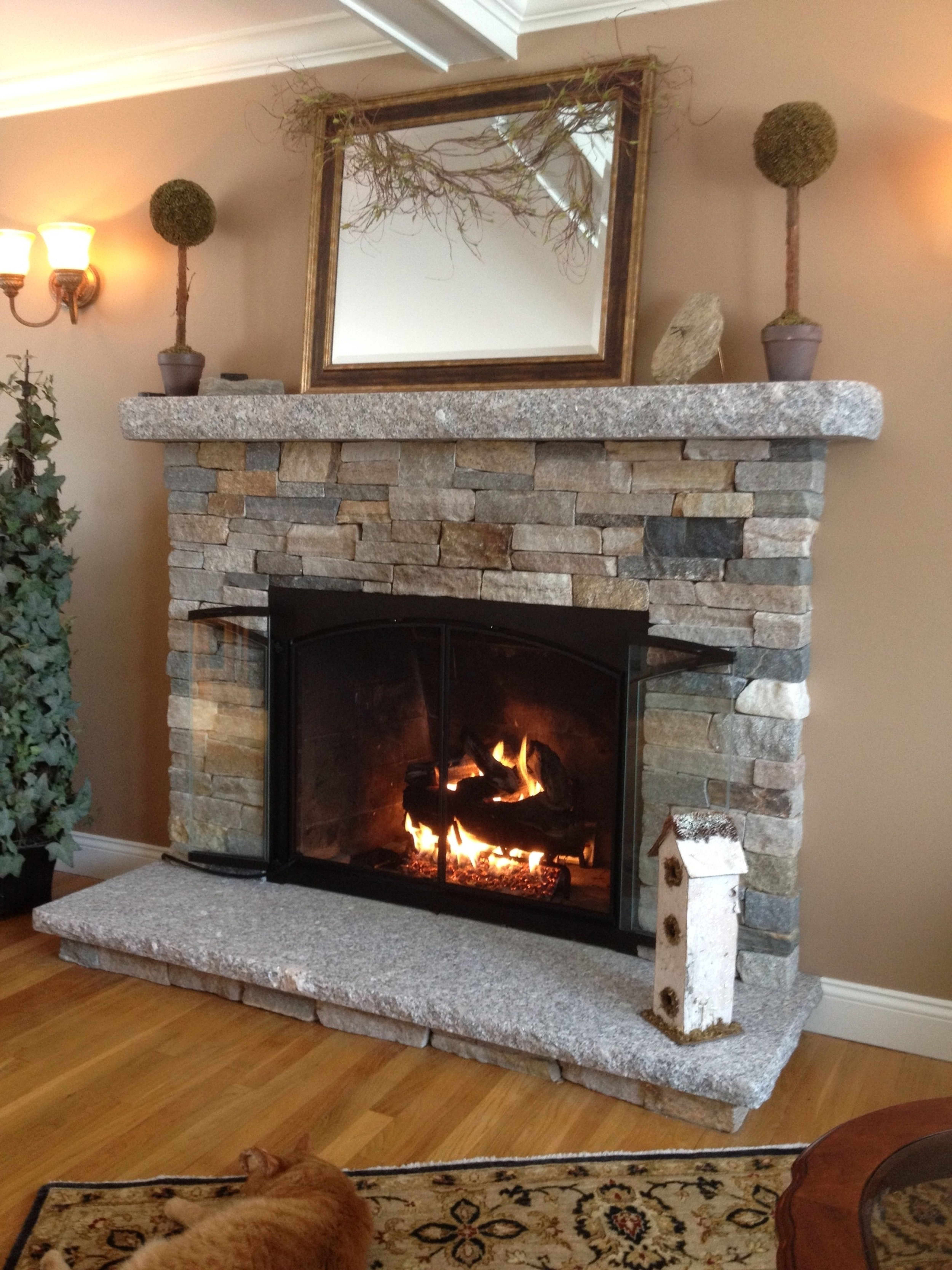 chic topiary trees with rectangle mirror and stone fireplace ideas plus christmas tree also wall sconce for beautiful modern living room design installing stone veneer fireplace mantelpiece accessorie