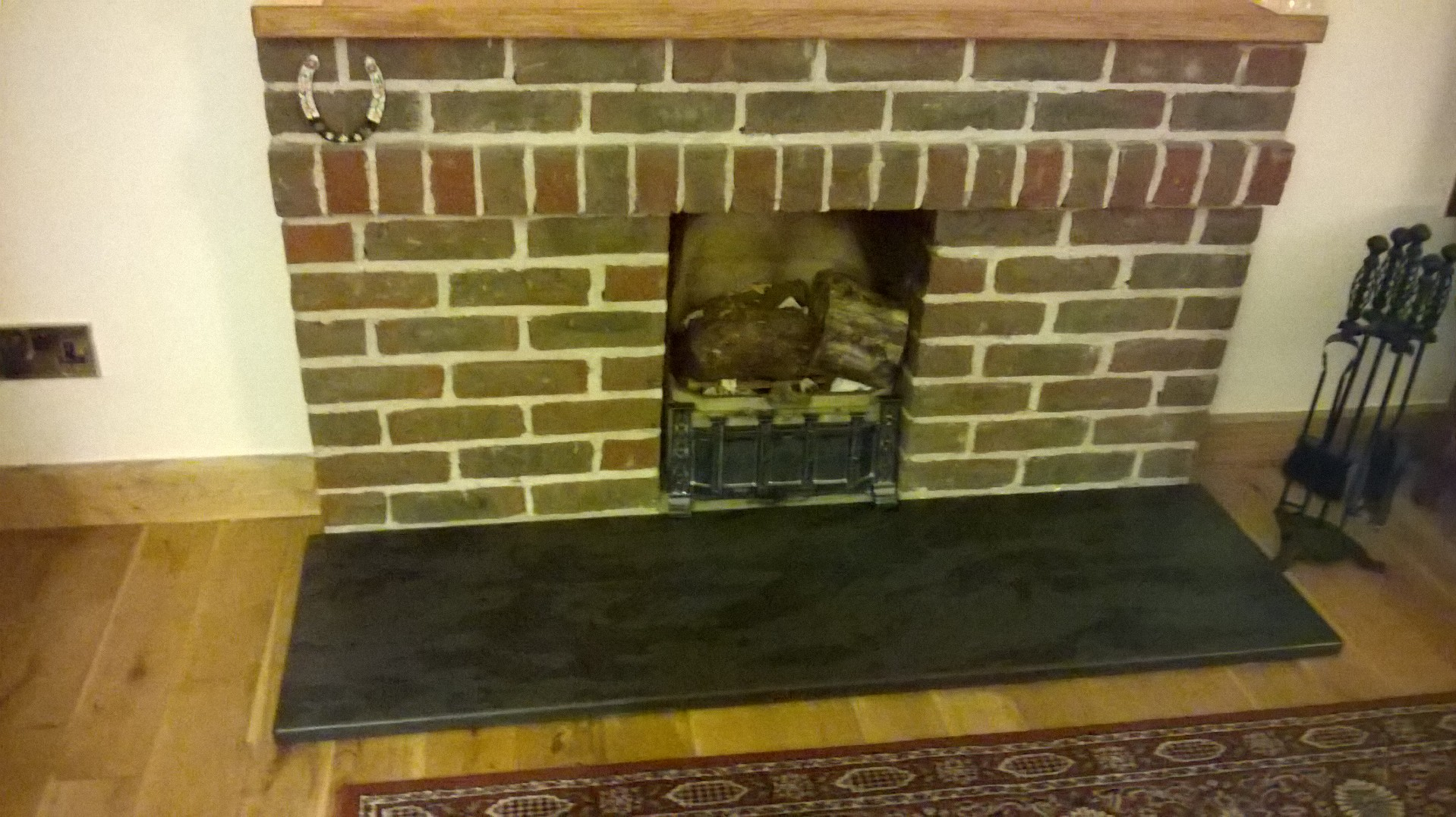 brick fireplace with black slate hearth