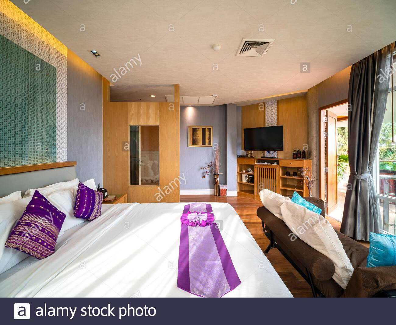 luxury room decor with brown wooden floor and furniture in warm light and window glasss for see view outside room of hotel resort in thailand 2AJRFDP
