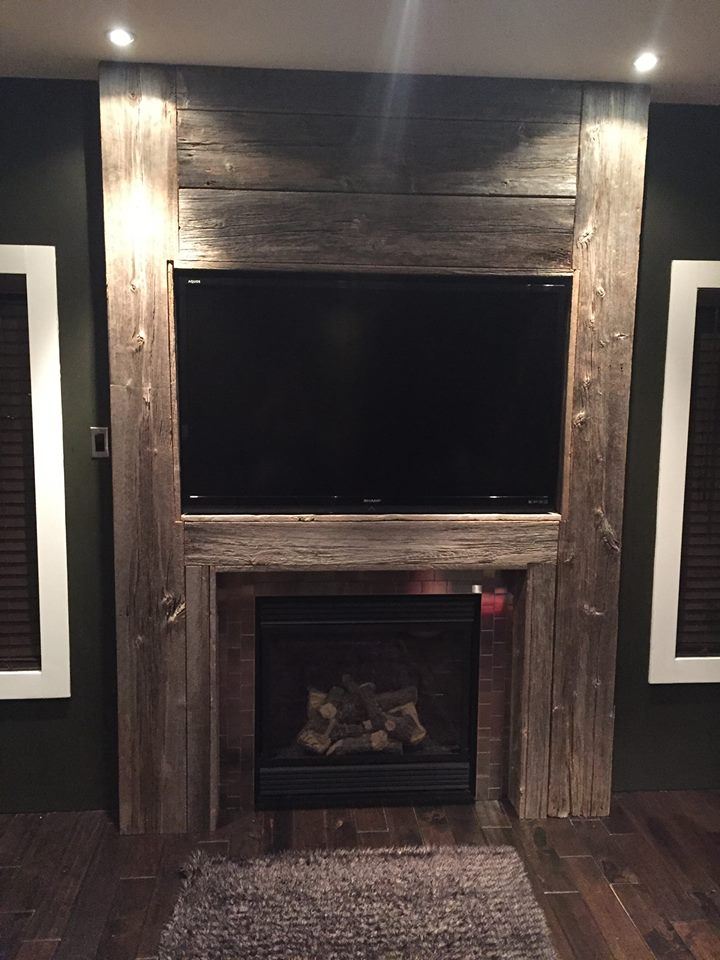 Floor to ceiling grey barnwood fireplace mantle with stainless steel tiles full