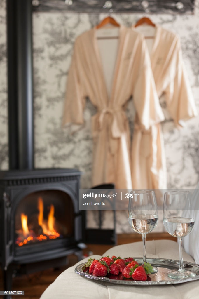 tray with wine and strawberries with robe and fireplace picture id