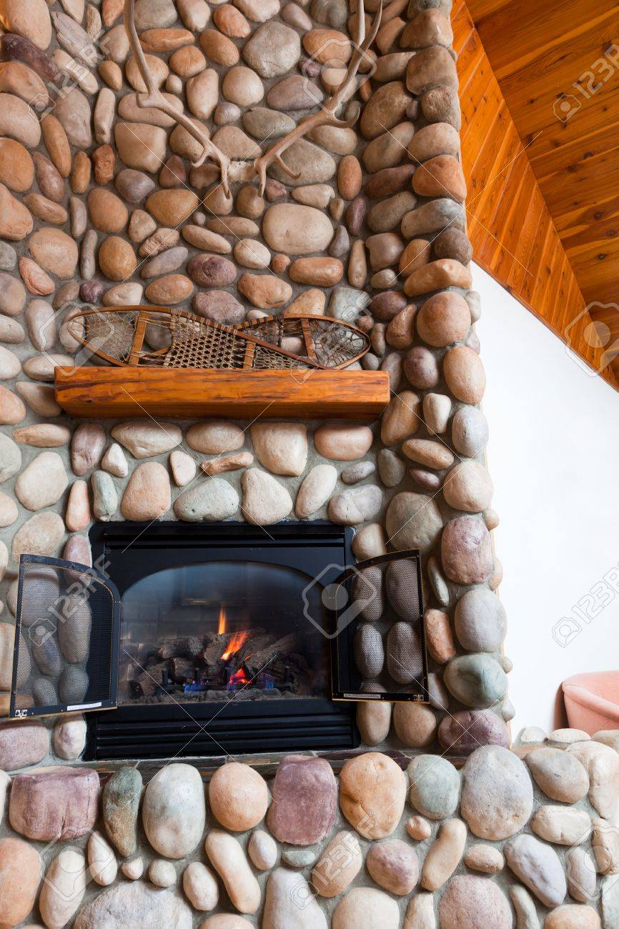 photo a gas fireplace set in colorful river rocks with a wooden mantle topped with vintage snowshoes and l
