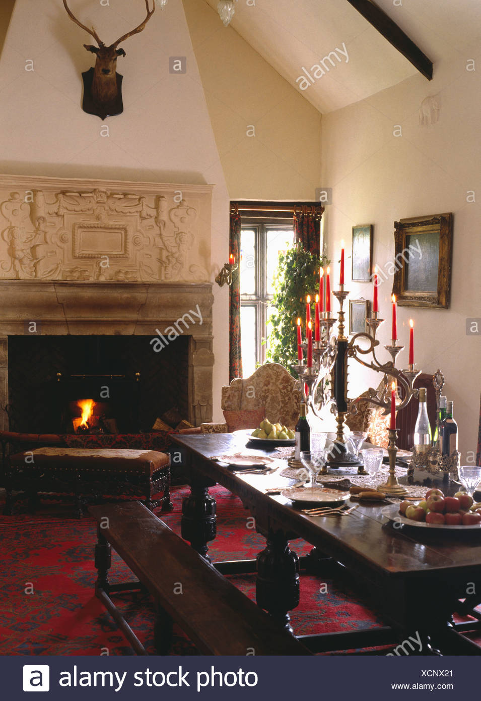 ornate overmantel on jacobean fireplace with fire lit in dining hall with oak table and benches XCNX21